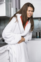 Young woman suffering from abdomen pain standing in kitchen