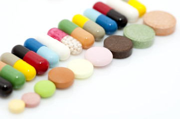 Assortment of capsules and tablets in row close up