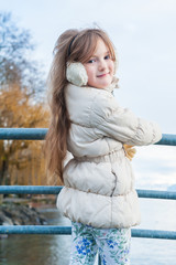 Outdoor portrait of a cute girl on a bridge on a nice winter day