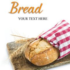 Barra de pan rústico envuelto en servilleta sobre una tabla