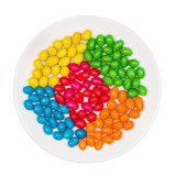 White plate full of sweet colorful candy isolated on a white
