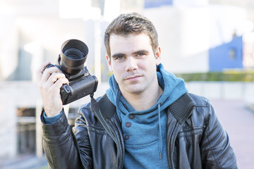 Portrait of photographer with camera, outdoor.