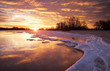 Winter landscape with lake and sunset fiery sky.