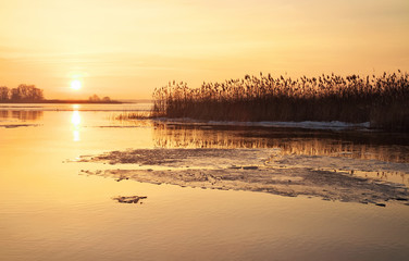 Winter landscape with river and sunset fiery sky.