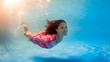 Underwater woman portrait wearing pink dress in swimming pool.