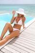 Beautiful chic woman sitting by pool in white bikini