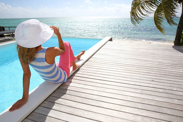 Rear view of fashion girl sitting by infinity pool