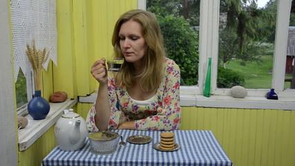 Woman drink herbal camomile tea in rural homestead veranda