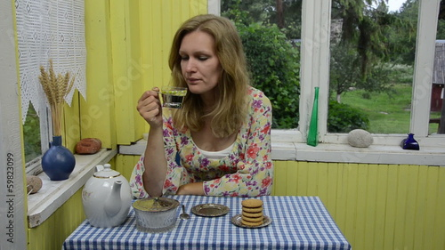 Woman drink herbal camomile tea in rural homestead veranda