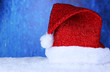 Santa hat on snow on blue background