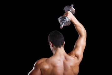 Strong man lifting weights against a dark background