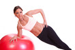 A beautiful young woman doing exercise on a red fitness ball