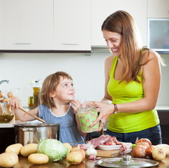 Smiling woman with baby cooking