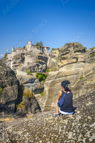 Beautiful girl is looking at famous monastery of Meteora