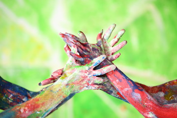 Interlacing female and male hands in paint of different colors