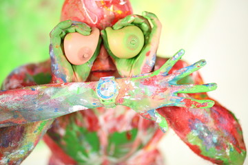 A man covered in paint held to eyes toy tits and female hand