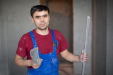 worker with spatula and level in workwear makes repairs poster