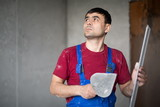 worker with spatula and level in workwear looking up poster