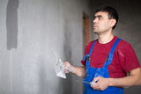 worker with spatula in workwear smears on wall putty poster