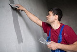 worker with spatula makes repairs smears on wall putty poster