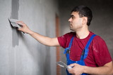 A worker with spatula in workwear makes repairs the wall poster