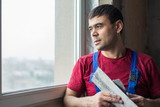 worker with spatula in workwear looks out window poster