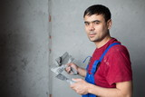 man with spatula in workwear makes repairs wall poster