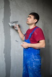 worker with spatula in workwear makes repairs wall poster
