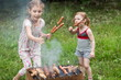 Two little girl making barbecue on grill on nature