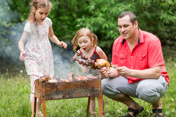 A family making barbecue on the grill on nature