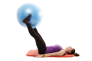 Woman holding a ball between legs and working her abdominal musc