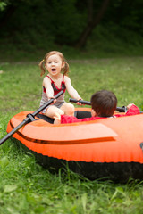 Two children plays with a boat and oars floating on the grass