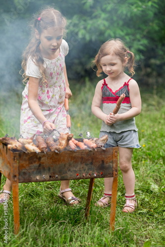 Two little girl making barbecue on the grill on nature