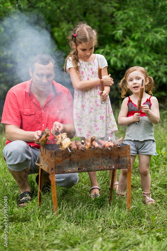 A family of three making barbecue on the grill