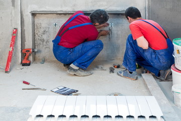 Two workers have made fastening in niche for radiators