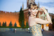 girl in dress with ribbon on hand standing next to Kremlin
