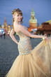 A smiling girl in dress on Red Square near the Kremlin