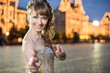 girl in dress standing on red square next to illuminate GUM