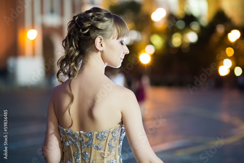 Young girl in a beautiful dress stands back
