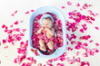 Baby girl lies in a bathtube with rose petals in studio