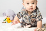 Baby boy in shirt with knitted toys in studio