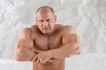 man with snow on body with arms on ice cubes
