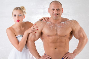 A strong man with snow on body and girl in white dress