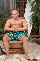 Muscular man on beach with surfboard near house
