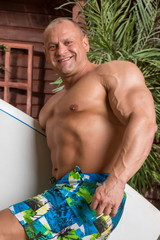 Muscular man on beach with surfboard near wooden house