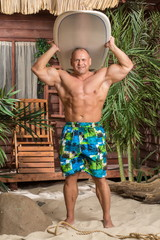 Muscular man on beach with a surfboard under the head