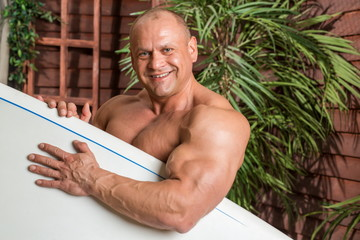 Smiling muscular man on a beach with a surfboard