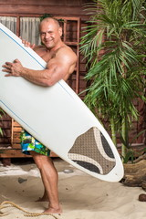 muscular man on a sandy beach with a surfboard