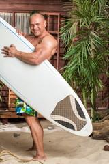 muscular man on a sandy beach with a surfboard