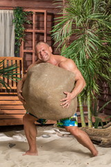 Muscular man picked up a large rock on the sandy beach